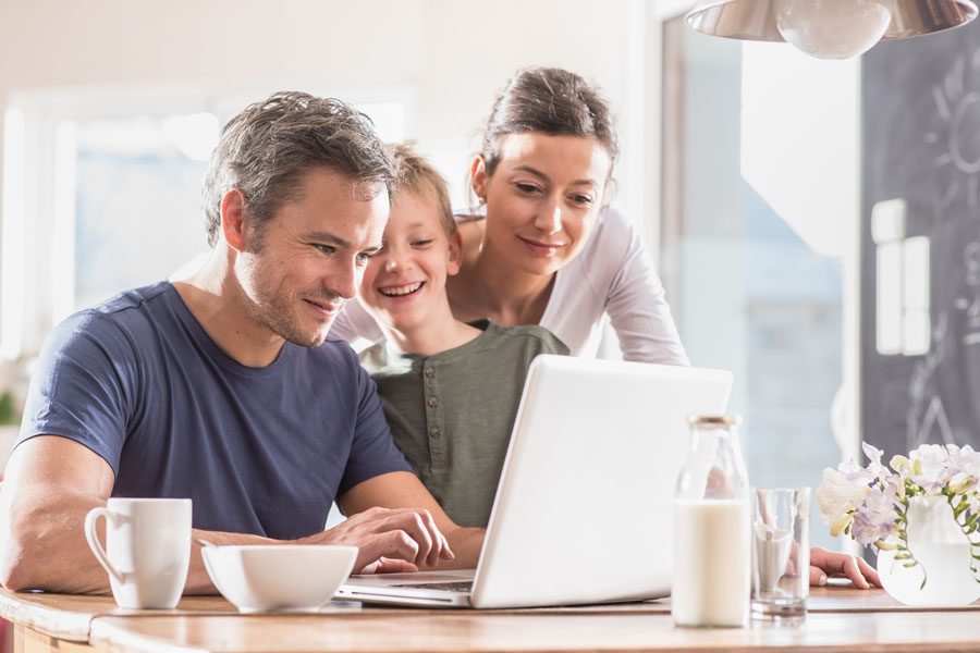 Report a Claim - Family Using the Computer at the Table
