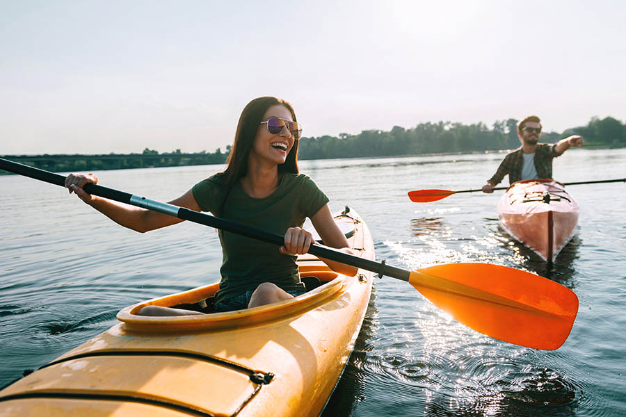 About Our Agency - Young Couple Paddle Single Kayaks on a Tree-Lined Lake, Smiling and Pointing up Ahead