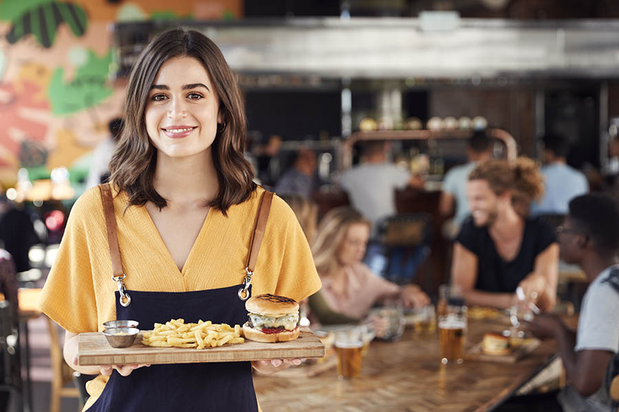 Business Insurance - Young Waitress Holds a Cheeseburger Meal on a Wooden Plank, as Customers Chat and Drink Beer in the Bustling Restaurant Behind Her