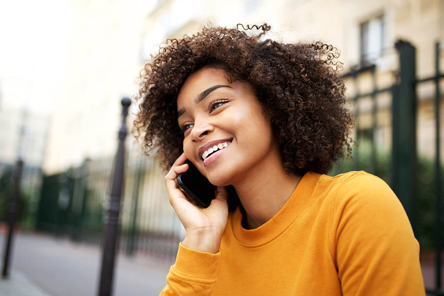 Contact Us - Smiling Black Woman in Yellow Sweater Sits Outside Making a Call on Her Cell Phone