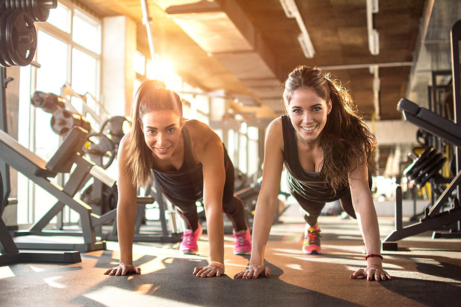 Employee Benefits - Two Smiling Female Friends Do Pushups Side by Side on the Floor of a Gym